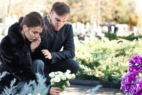Couple visiting grave of loved one